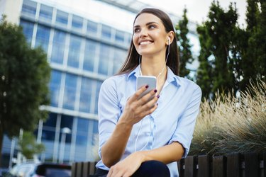 Young businesswoman holding mobile phone and smiling