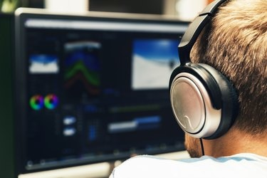 man doing video editing on computer with headphones on