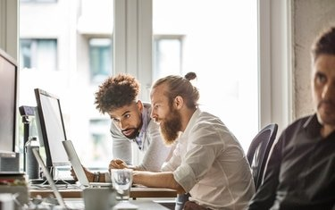 Businessmen discussing over laptop in office