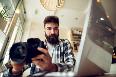 Young photographer beard man editing pictures at his home.