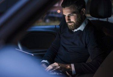 Businessman using laptop in car at night