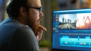 Male Video Editor Works with Footage and Sound on His Personal Computer. He Works in a Cool Office Loft.