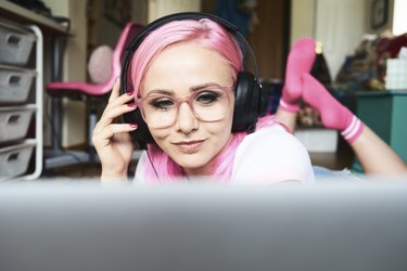Young woman with pink hair listening to music via laptop at home
