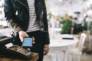Woman Paying With Smartphone.