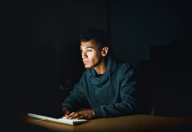 Young man working on computer late at night