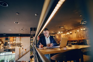 Smiling middle-aged businessman writing down something in agenda while sitting in cafe at the evening. On table coffee and laptop.
