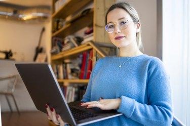 Female higher education student sitting on university stairway using laptop, portrait