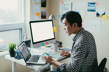 Asian man working at a comptuer