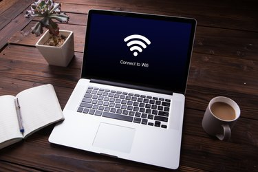 View of wi-fi connection on the laptop / computer screen with office equipment on wooden desk background