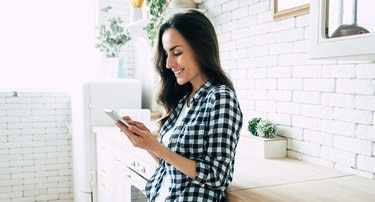 Beautiful cute smiling woman is using smart phone on the kitchen at home.