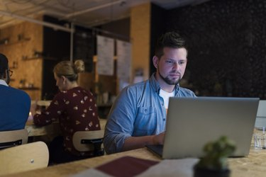 Businessman working late using laptop in cafe