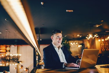 Smiling middle-aged businessman using laptop and having earphones in ears while sitting in cafe at the evening.