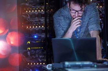 Focused male IT technician working at laptop in dark server room