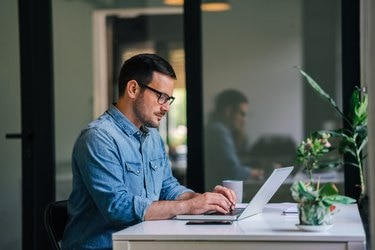 Serious pensive thoughtful focused young casual businessman or entrepreneur in office looking at and working with laptop making and typing serious important business email
