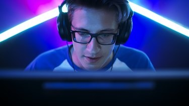 Professional Gamer Plays in MMORPG/ Strategy/ Shooter Video Game on His Computer. He's Participating in Online Cyber Games Tournament, Plays at Home, or in Internet Cafe. He Wears Glasses and Gaming Headphones, Talks into Microphone.