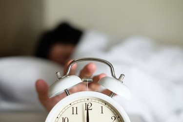 Cropped Hand Of Person Turning Off Alarm Clock
