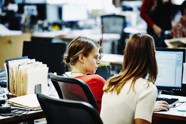 Two businesswomen sitting working on computer