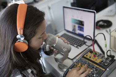 Teenage girl with headphones singing, recording music at microphone equipment