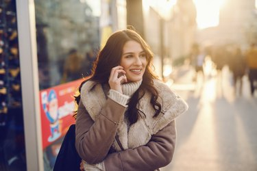 Close up of Caucasian woman with long brown hair dressed in coat using smart phone for call while standing on the street on cold weather. Back light.