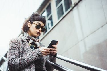 Winter portrait of a young woman in the city texting