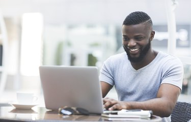 Smiling african man textmessaging on laptop in cafe
