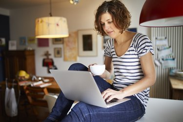 Portrait of mature woman sitting on kitchen table using laptop