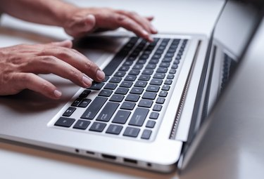 Close-up of man hands typing on the laptop