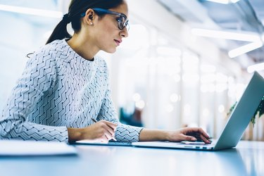 Professional administrative manage in spectacles for eyes protection checking content of company website on laptop computer, serious female secretary making booking on netbook working in office