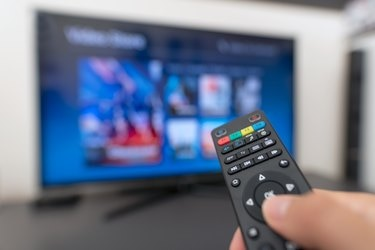 Multimedia streaming concept. Hand holding remote control