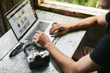 Male on laptop in beach hut