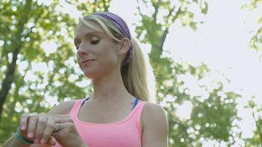 Blonde athletic woman checking fitbit device after running off road