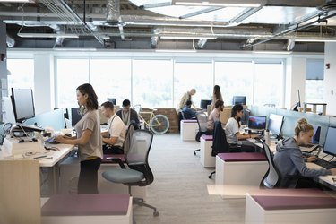 Creative business people working at computers in open plan office