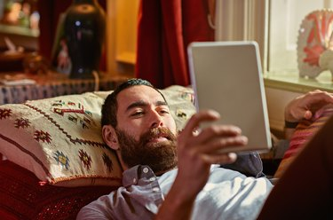 Young man relaxing with a digital tablet