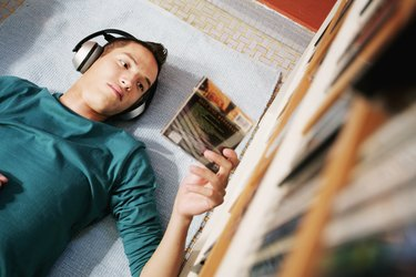 Young Man Reading CD Case