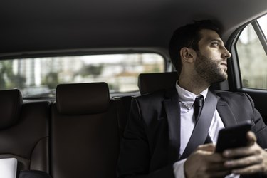 Businessman using cellphone in a cab and looking through window