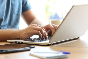 Man hands typing on a laptop keyboard on a desk