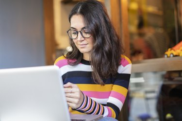 Beautiful Woman with Long Black Hair and Glasses Using a Laptop and Looking to Mobile Phone