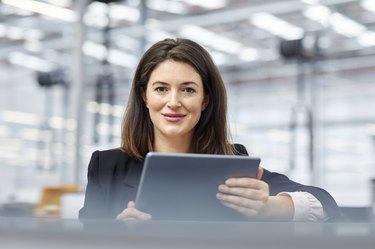 Female manager holding digital tablet in car plant