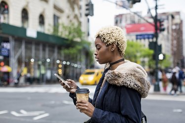 USA, New York City, fashionable young woman with coffee to go looking at cell phone on the street