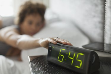Woman reaching for snooze button on alarm clock.