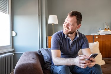 Young man is using smartphone at home