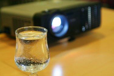 glass of water on table with projector behind