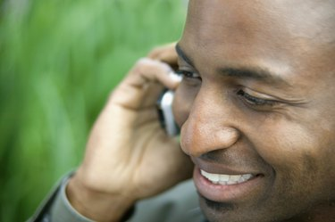 Close-up of a young man smiling talking on a mobile phone