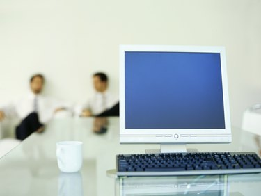 Close-up of a computer with two businessmen sitting in the background