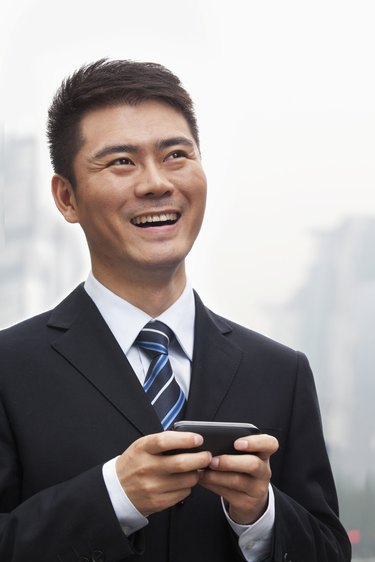 Young Businessman Smiling and Using a Smart Phone