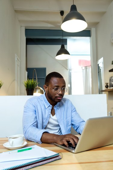 Handsome young black man working with laptop at home.