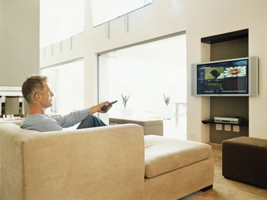 Mature Man Sits Watching TV in a Modern Home Interior
