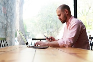 Young hipster busy using smart phone at office desk