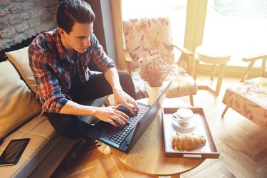 Young man sitting at a cafe, using a laptop, drinking espresso