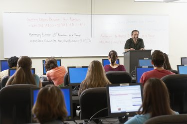 Rear view of a group of students sitting in front of computer monitors
